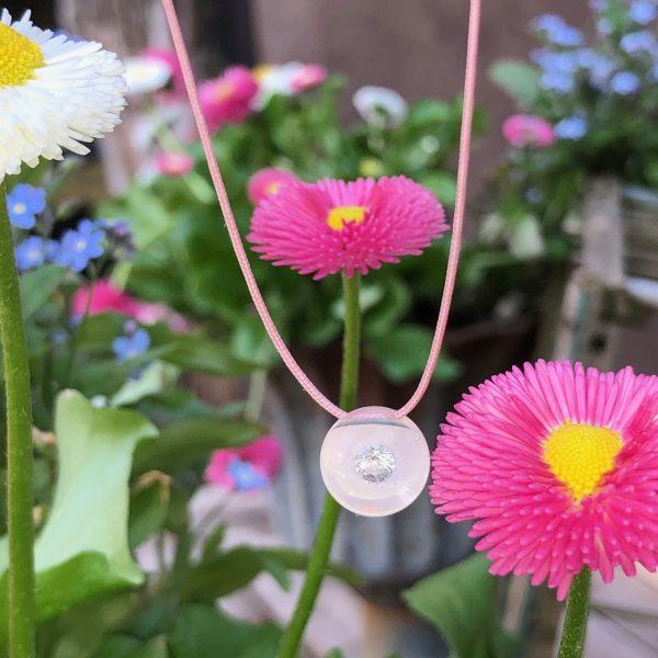 """Aus der limitierten Glasklar - Serie """"25 Jahre schmuckwerk - ein Fest in rosé"""" ist dies unser letztes Brillantkugel-Collier in rosa unterlegt. Erleben Sie eine neue Schmuckdimension. Der Brillant schwebt völlig frei in einer Kugel aus Glas und reflektiert strahlend das Licht. Ein einmaliges handwerkliches Kunststück. Zudem wird der Stein durch den Lupeneffekt um das 3-fache vergrößert. Haben Sie so etwas schon einmal gesehen? Wenn nicht, kommen Sie uns doch einfach einmal besuchen."""