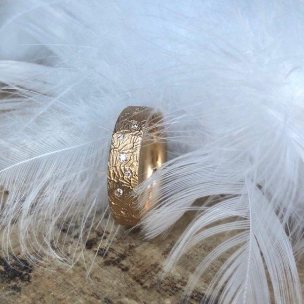 Ausgefallener Schmuckring oder Trauring von der Goldschmiedin Marion Knorr - wilde ehe ringe - aus Roségold 750/- mit 7 kleinen, eingestreuten Brillanten, die Oberfläche des Ringes erinnert an Ihre Reisen und den Blick aus dem Flugzeug auf das Meer, wie kleine Wellen wirkt die Struktur dieses wunderschönen, gradlinigen Ringes