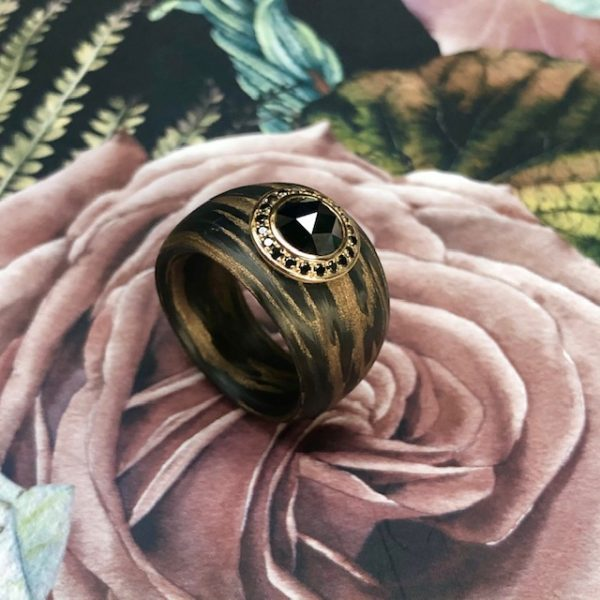 Aufregender breiter, konisch verlaufender Ring aus Carbon Bronze von Schwab mit einem großen schwarzen Diamanten im Rosenschliff, 1,5ct umrandet von kleinen schwarzen Brillanten in 750/-Gelbgold gefasst. Designschmuck. Ringweite 55