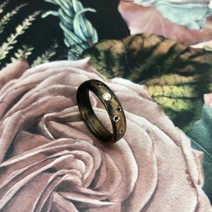 Ein Carbon Bronze Ring von SCHWAB mit naturfarbenen und schwarzen Brillanten in Gelbgold gefasst und wie ein Sternenhimmel eingestreut