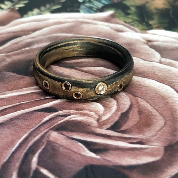 Carbon Bronze Ring von SCHWAB mit naturfarbenen und schwarzen Brillanten in Gelbgold gefasst, Ring liegend