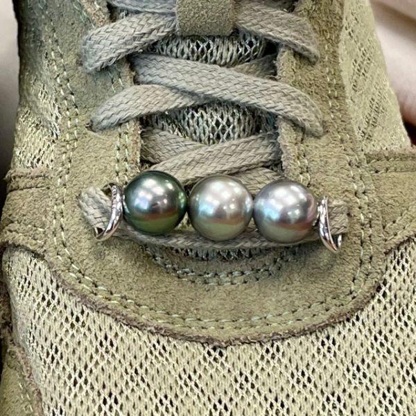 """WoW, das gab es noch nie! Was für ein wertvolles Highlight für Ihr Outfit... Dieser brandneue Schmuck für Ihre Lieblingssneaker lässt sich nicht übersehen. Die wunderschönen Farben der Tahitiperlen passen mit ihren grün-grau-beige-silbrigen Tönen zu fast jedem Schuh und sowieso zu jeder Garderobe. Heute sportlich, morgen schick - zeigen Sie uns gerne Ihre Kreationen. Ein perfektes Geschenk für Perlliebhaber:innen die schon fast alles haben. #styleyoursneaker GELLNER Sneaker Accessoiries 3 Tahiti-Zuchtperlen, multifarben, oval, 11-12mm Sterlingsilberbügel 925/- weiss rhodiniert und poliert Perlen sind Naturprodukte und können farblich variieren leichte Farbunterschiede im Vergleich zum Foto sind üblich, da Perlen Unikate sind Die Woden-Sneaker sind eine freundliche Leihgabe von """"Lieblingsstücke"""" in Gevelsberg"""