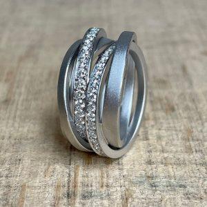 Schmuckwerk-Diamantenfieber-Saturn-Ring-Weissgold-3-Ringe-2-Brillantringe-SR126WG Ordnung in der Unordnung. Jeder Ring besteht aus unterschiedlichsten Einzelringen. Schmaler, stärker oder schräger. Mit oder ohne Diamantlinien, die unter den Ringen verschwinden und wieder auftauchen. Sichtbares und Unsichtbares, ein ungeordnetes Durcheinander, das zur wunderschönen Einheit wird. Dreht man den Ring, sieht er immer wieder anders aus und erinnert an Unendlichkeit.
