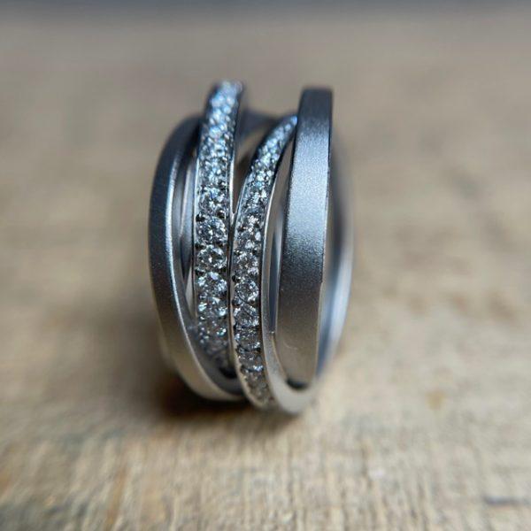 Schmuckwerk Saturn Ring Ein Dreh für die Unendlichkeit Ordnung in der Unordnung. Jeder Ring besteht aus unterschiedlichsten Einzelringen. Schmaler, stärker oder schräger. Mit oder ohne Diamantlinien, die unter den Ringen verschwinden und wieder auftauchen. Sichtbares und Unsichtbares, ein ungeordnetes Durcheinander, das zur wunderschönen Einheit wird. Dreht man den Ring, sieht er immer wieder anders aus und erinnert an Unendlichkeit.SR126WG