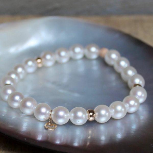 Powerarmband aus 22 feinen und schimmernden Akoya-Perlen mit 5 Rosegoldelementen und kleinem Gellner-Logo auf Gummi gezogen