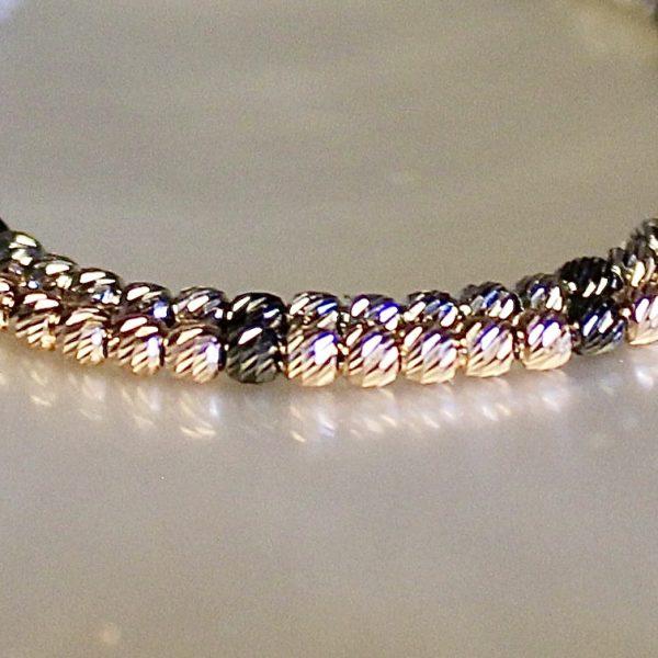Vergrösserung der facettierten Goldkugeln des 14k Armbands in Rotgold-Schwarz und Weißgold-Schwarz