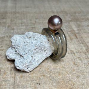 Apollo Ring von der Designerin Monika Seitter aus hellgrauem Silikon mit Rosegold-Element und brauner Tahitiperle, dreifach gewickelte