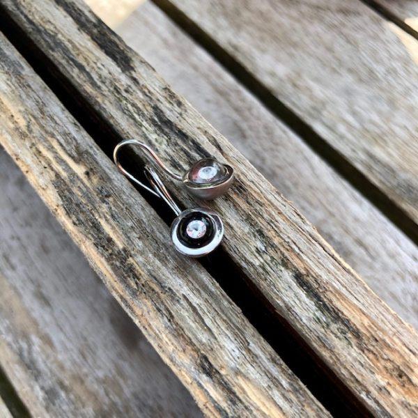 Die Glaskugeln werden von Edelstahl-Schalen gehalten und schwingen an einem Schwanenhals am Ohr. Erleben Sie eine neue Schmuckdimension. Der Brillant schwebt völlig frei in einer Kugel aus Glas und reflektiert strahlend das Licht. Ein einmaliges handwerkliches Kunststück. Zudem wird der Stein durch den Lupeneffekt um das 3-fache vergrößert. Haben Sie so etwas schon einmal gesehen? Wenn nicht, kommen Sie uns doch einfach einmal besuchen.