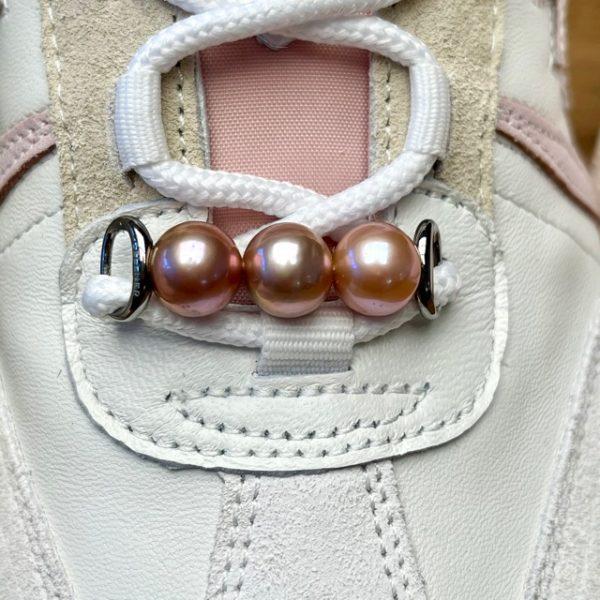 """WoW, das gab es noch nie! Was für ein wertvolles Highlight für Ihr Outfit... Dieser brandneue Schmuck für Ihre Lieblingssneaker ist nicht zu übersehen. Die wunderschönen natürlichen Rosé-Töne der Ming-Perlen harmonieren mit vielen Farben und ihr Schimmer kommt besonders auf hellen Schuhen zur Geltung. Tragen Sie dieses Accessoire wie Sie wollen:Heute sportlich, morgen schick - zeigen Sie uns gerne Ihre Kreationen. Ein perfektes Geschenk für Perlliebhaber:innen die schon fast alles haben. #styleyoursneaker GELLNER Sneaker Accessoiries 3 Ming Zucht-Perlen (Süßwasser) rosa, semi rund 11-12mm Sterlingsilberbügel 925/- schwarz rhodiniert und poliert Perlen sind Naturprodukte und können farblich variieren leichte Farbunterschiede im Vergleich zum Foto sind üblich, da Perlen Unikate sind Die Premiata-Sneaker sind eine freundliche Leihgabe von """"Lieblingsstücke"""" in Gevelsberg"""