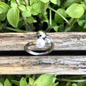 Schmuckwerk Perlenrausch Drilling Ring aus Edelstahl, Ein jugendliches Designstück, welches nicht durch sein Volumen besticht, sondern durch die verschiedenen Größen der 3 kugeligen Elemente - der Perle, einer mattierten und einer polierten Stahlkugel. Aller guten Dinge sind drei.