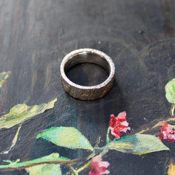 Marion Knorr Roh Ring, 8 mm breit und 2 mm hoch, aus Silber hell rhodiniert, wilde ehe ringe, die Oberfläche ist roh wie eine grob verputzte Wand, die Oberfläche gestalten Sie durch Ihr Tragen selber. Ring liegend.