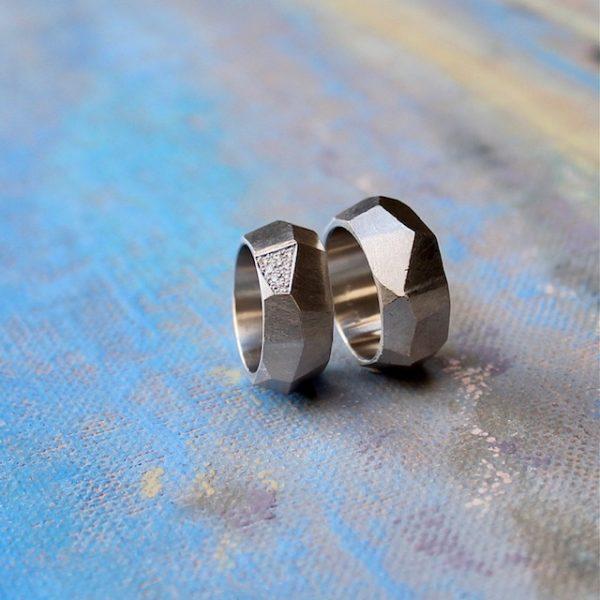 Marion Knorr Wellenbrecher Ringe aus 925 Sterlingsilber, aus der Trauring-Kollektion wilde ehe ringe. Der Ring hat die Form und Struktur eines Felsen am Strand, der die heran rollenden und bedrohenden Wellen bricht und sanft in die Bucht weiterleitet. Ein Schutz für das Liebespaar, der die Bedrohung von außen mildert. Die Form dient ergonomischen Zwecken, da der Ring am Finger in eine erstaunlich bequeme Form rutscht. Aus der Kollektion wilde ehe ringe