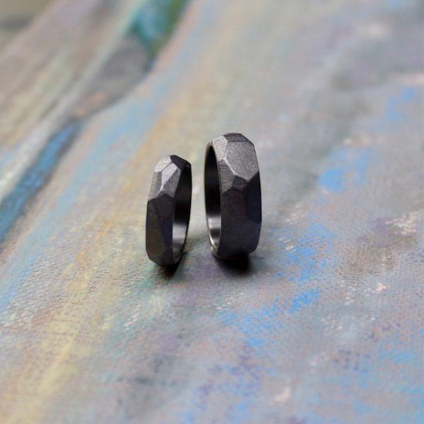 Marion Knorr Wellenbrecher Ringe aus Tantal, aus der Trauring-Kollektion wilde ehe ringe. Der Ring hat die Form und Struktur eines Felsen am Strand, der die heran rollenden und bedrohenden Wellen bricht und sanft in die Bucht weiterleitet. Ein Schutz für das Liebespaar, der die Bedrohung von außen mildert. Die Form dient ergonomischen Zwecken, da der Ring am Finger in eine erstaunlich bequeme Form rutscht. Hier stehend abgebildet.