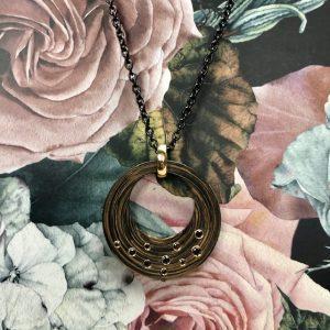 4cm grosser, runder Carbon Bronze Anhänger mit schwarzen Diamanten in Gelbgold gefasst, an einem Goldclip befestigt an einer schwarzen Edelstahlkette mit Gelbgoldkarabiner und Zwischenöse