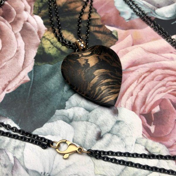 Das 33mm große Herz aus Carbon / Bronze schwingt an einer sehr formschönen, runden, goldenen Öse, bestückt mit schwarzen Brillanten und ist verbunden mit einer ebenso besonderen, doppelreihigen Rundanker-Kette aus schwarz beschichtetem Edelstahl, welche von einem kräftigen, mattierten Gelbgoldkarabiner geschlossen wird.Eine weitere Besonderheit dieses leichten, angenehmen und wertvollen Handschmeichlers sind die unterschiedlich gemaserten Seiten.