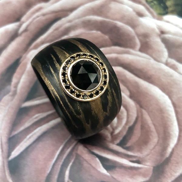 Aufregender breiter, konisch verlaufender Ring aus Carbon Bronze von Schwab mit einem großen schwarzen Diamanten im Rosenschliff, 1,5 ct umrandet von kleinen schwarzen Brillanten in 750/-Gelbgold gefasst. Designschmuck. Ringweite 55